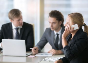 Businesswoman making call, attending business meeting. Group of colleagues or subordinates partaking in powerful training activities, moving online marketing to the next level, important phone talk